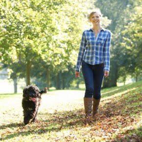 Young woman and her dog walking in park